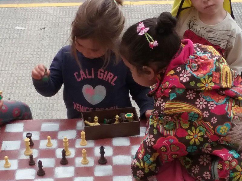 Alumnos jugando al ajedrez en el patio del recreo