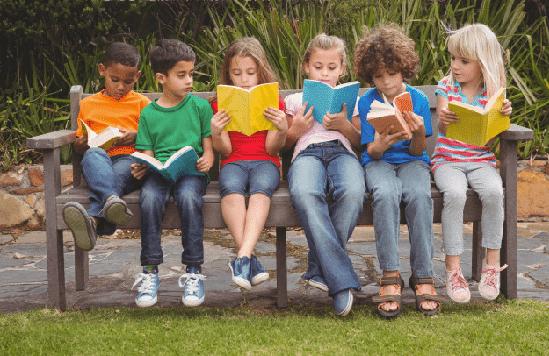 niños leyendo en banco