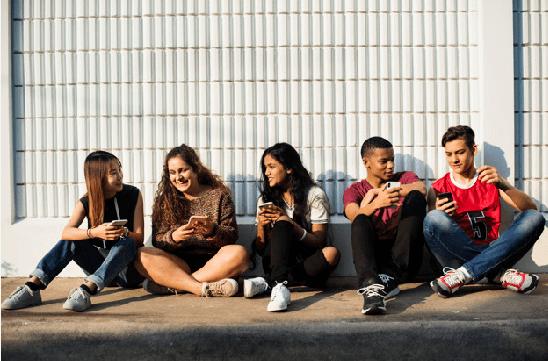Grupo de adolescentes viendo el móvil