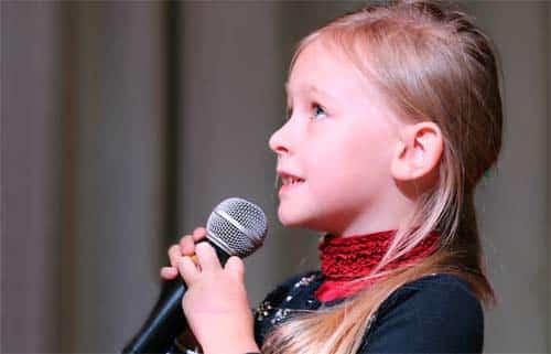 Niña con micrófono: oratoria en las aulas