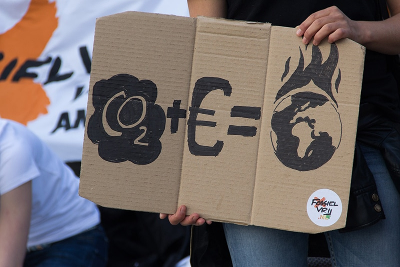 Pancarta que denuncia la emisión de CO2 por los intereses de las empresas.