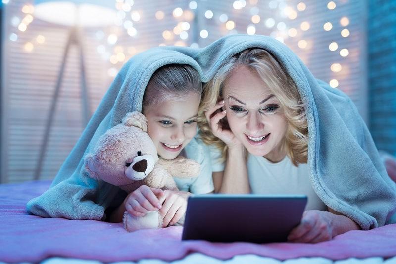 Una niña ve una película con su abuela en una tableta