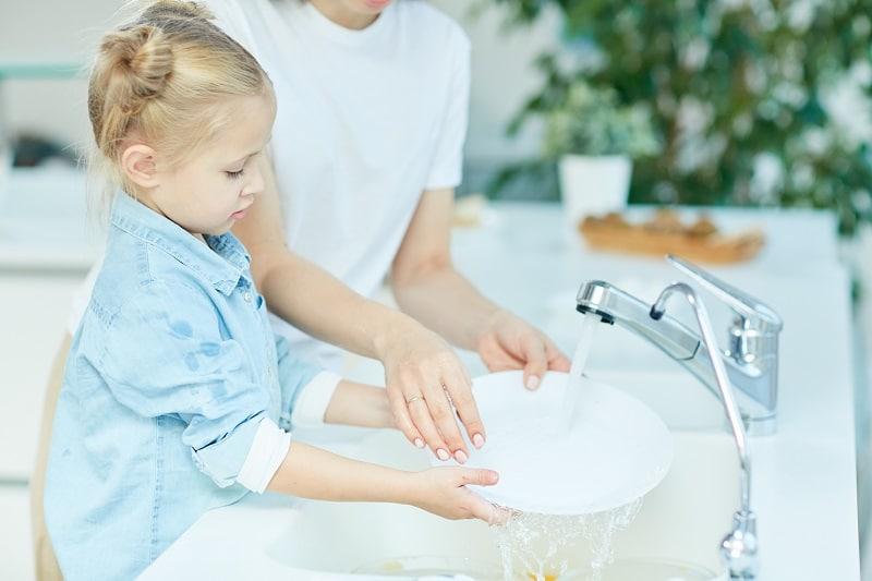 Una niña friega los platos con la ayuda de un adulto