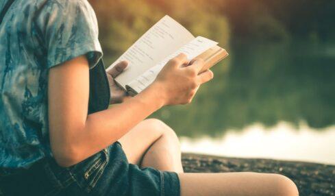 mujer lee al lado de un río