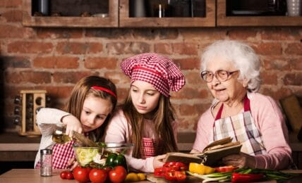 Dos niñas siguen una receta con su abuela