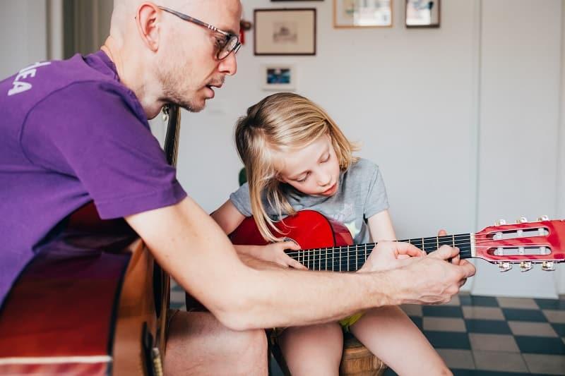 un padre le enseña a su hija a tocar la guitarra, pasando tiempo en familia