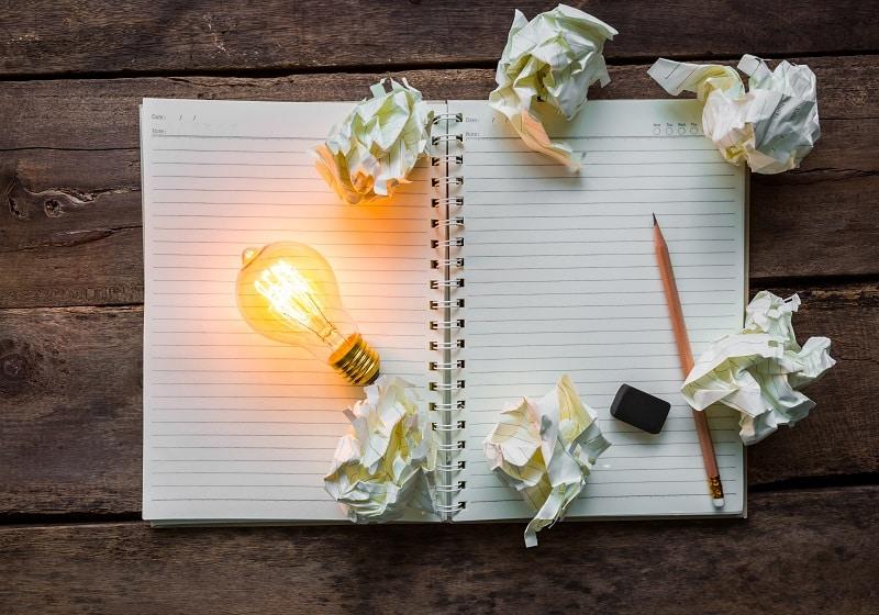 el error como parte del aprendizaje - un cuaderno con hojas arrancadas, un lapiz, un borrados, y una bombilla encendida.