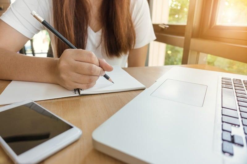 los retos de los examenes online. una alumna toma notas delante del ordenador.