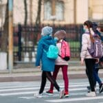 Niños de camino al colegio con mascarilla