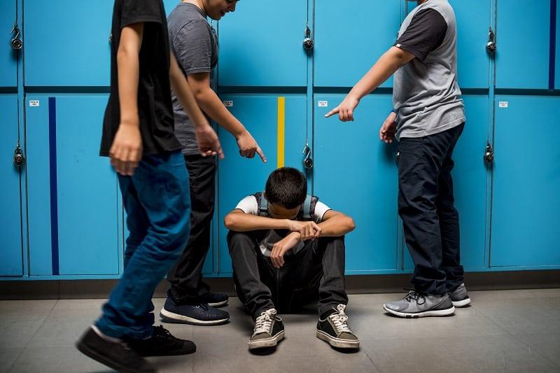 Unos niños acosan a otro que está sentado en el suelo. La educación emocional puede prevenir estas situaciones de acoso.