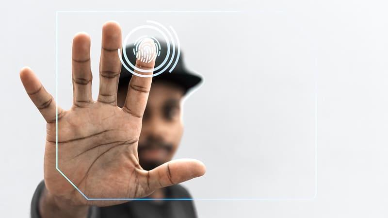Un hombre desbloquea un dispositivo con una contraseña segura y su huella dactilar.