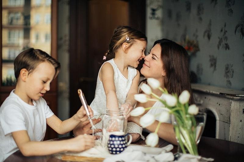 una madre pasa tiempo en familia con sus hijos - las familias mejoran la comunicación en confinamiento