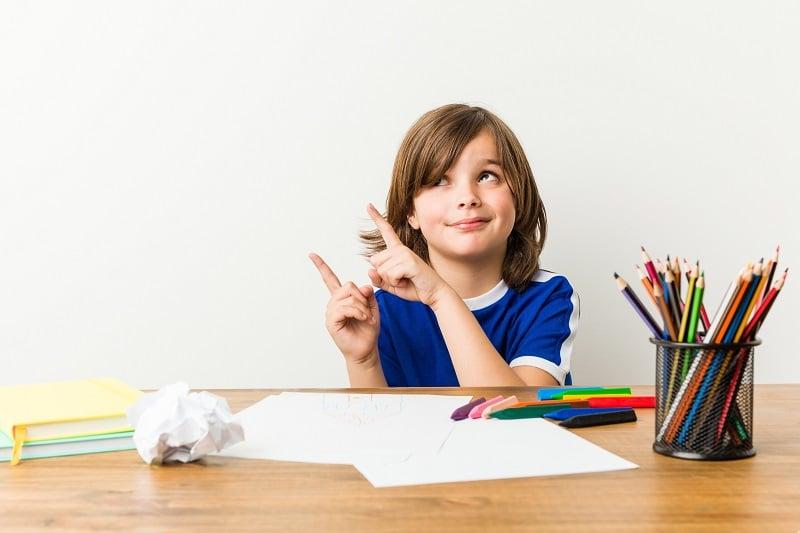 Niño haciendo deberes en verano distraído - repaso y descanso en vacaciones
