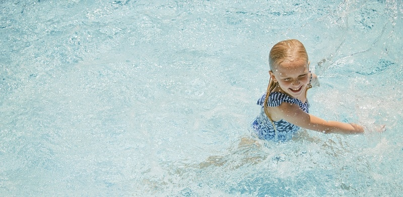 una niña se baña en la piscina en verano - repaso y descanso en vacaciones