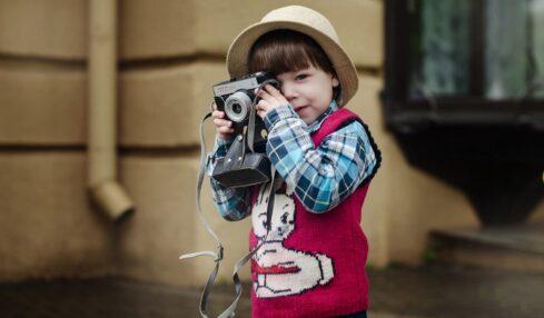 Un niño aprende a usar una cámara de fotos