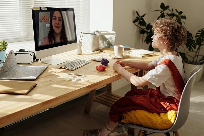 Un niño trabaja mientras escucha a su profesora - docencia online