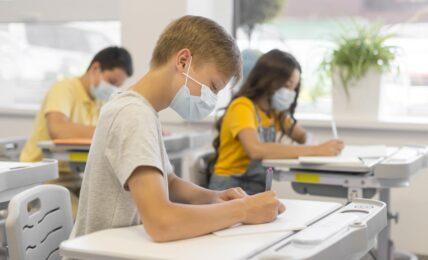 Niños estudiando en clase con mascarilla