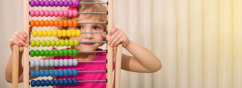 Una niña mira através de un ábaco