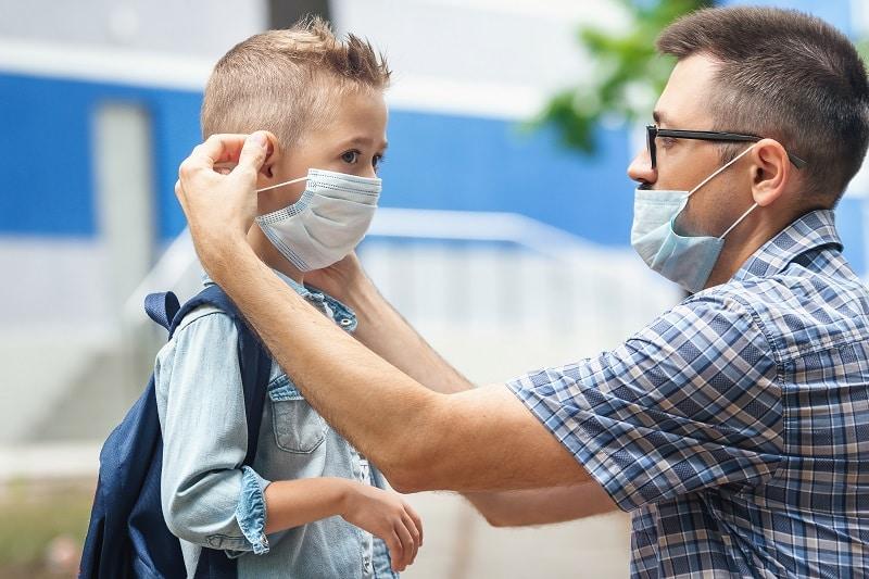 Un padre le coloca la mascarilla a su hijo en la vuelta al cole