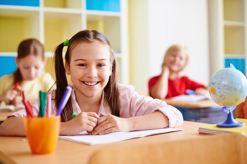 Niños en clase atendiendo a la profesora.