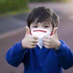Niño con mascarilla hace el signo de todo ok con los pulgares hacia arriba