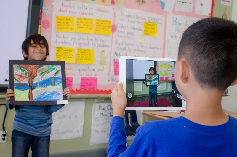 Dos estudiantes suben una foto de un proyecto a ClassDojo