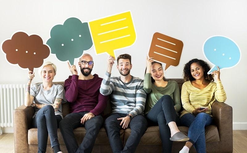 Mejora la comunicación entre centro y familias - un grupo de personas en un sofá sujetan burbujas de conversación