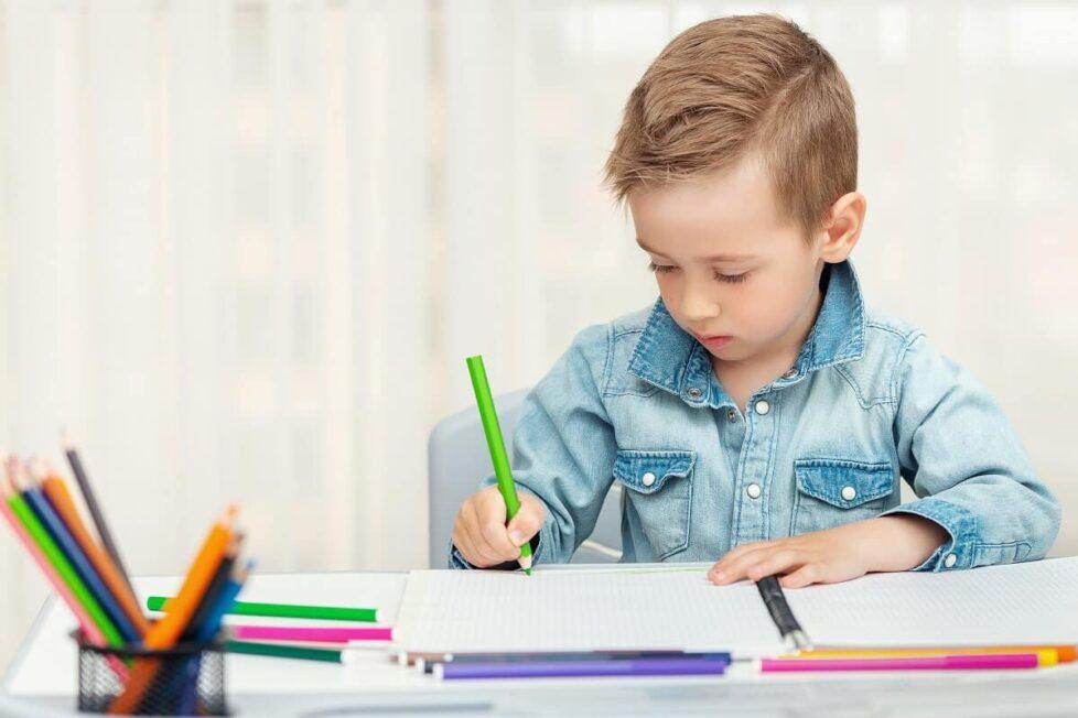 un niño escribe a mano con un lapicero de color verde