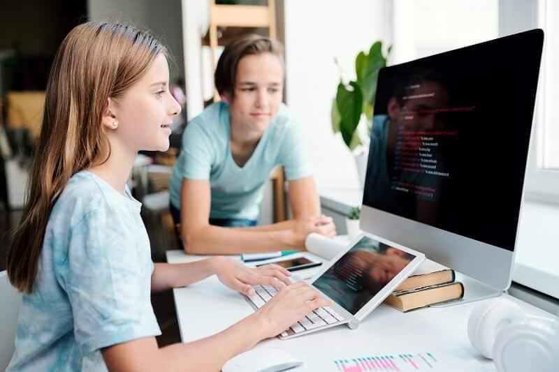 Una niña está escribiendo con el teclado. Escribir a mano mejora el aprendizaje.