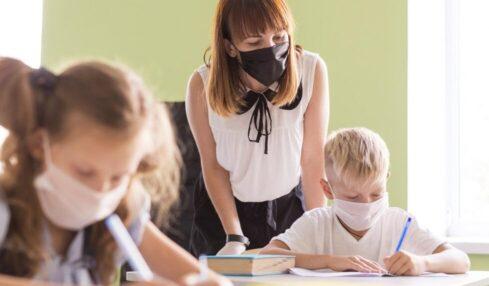 Profesora y alumnos con mascarilla en el aula