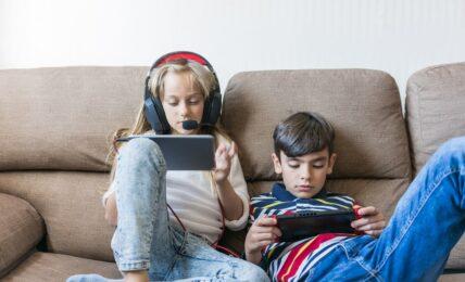 Niños juegan con consolas portátiles