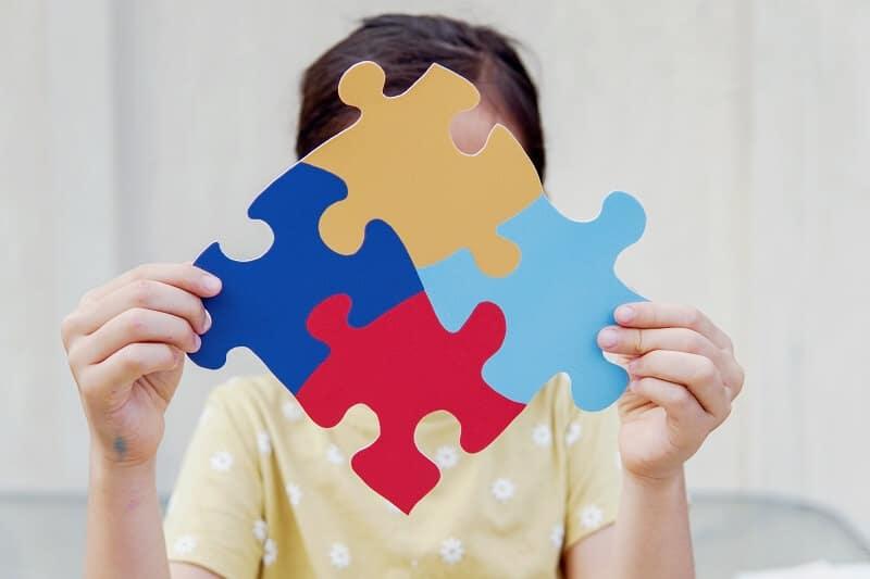 Una niña sujeta un puzle, símbolo del TEA