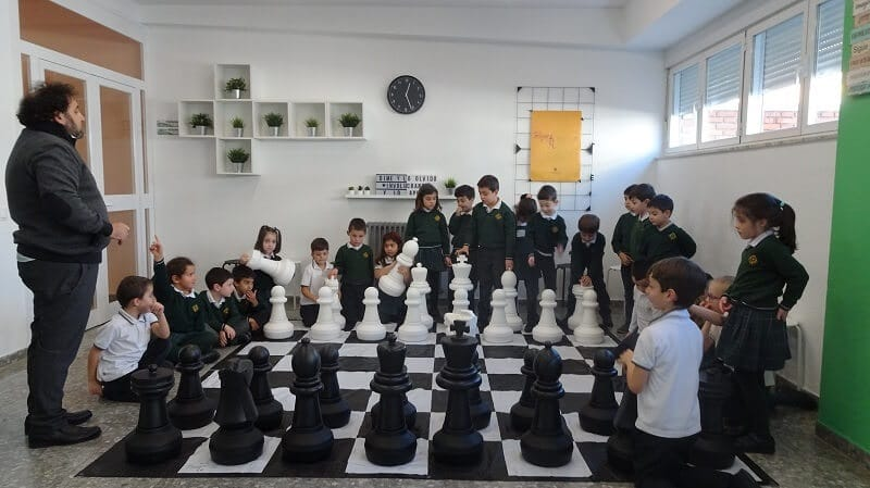Niños juegan al ajedrez en el aula todos juntos
