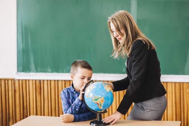 Un niño se concentra mientras mira la bola del mundo con su profesora