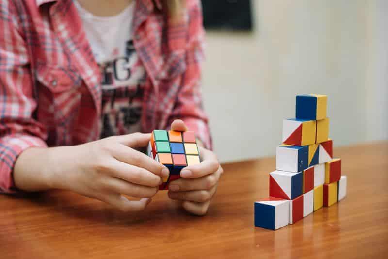 Una niña se concentra mientras juega con un cubo de rubik.