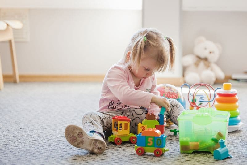 Una niña se relaja mientras juega con juguetes en el suelo  - pautas para mejorar el aprendizaje de alumnos TEA