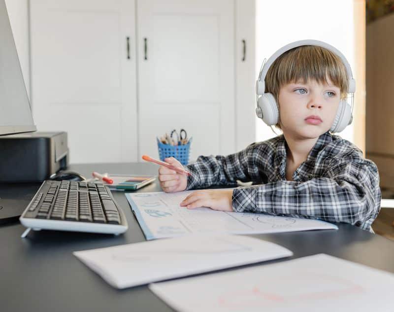 Un niño pequeño se distrae en una clase online - educación presencial