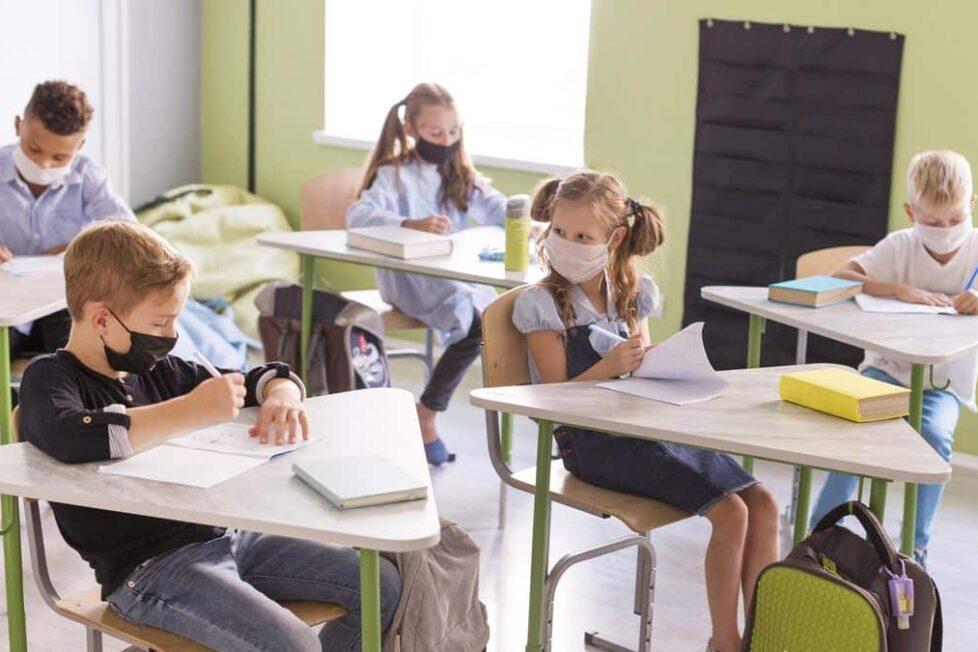 niños en una clase presencial con mascarilla