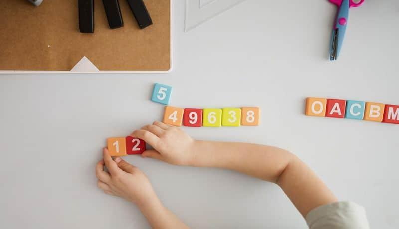 un niño juega con bloques con números y letras