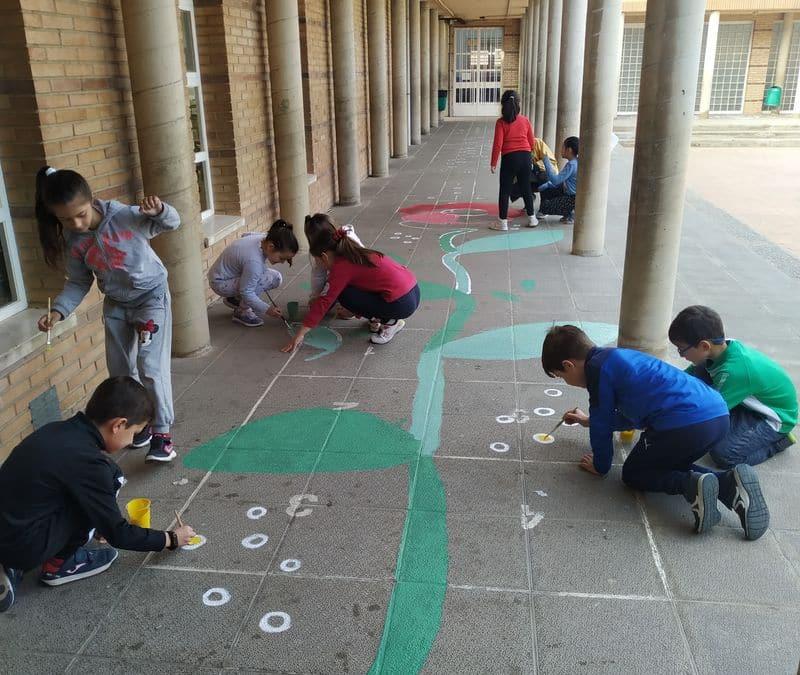 Los alumnos pintan en el suelo del patio una flor entre todos