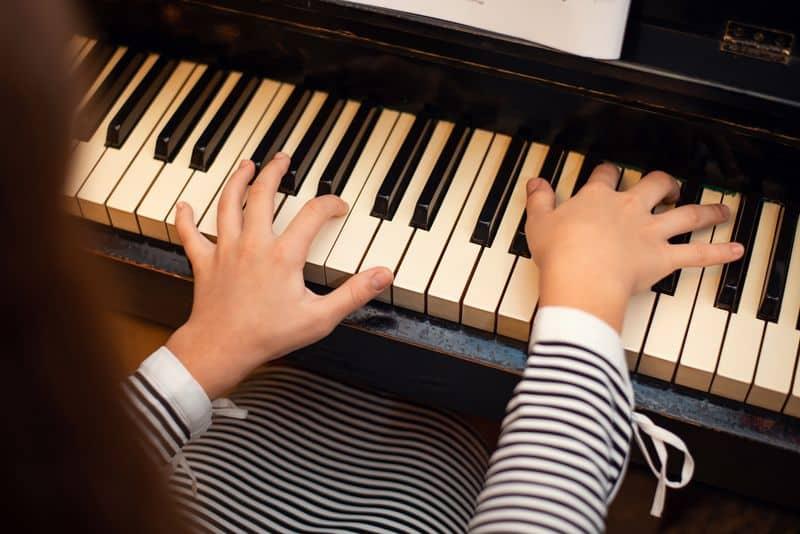Una niña toca el piano. Educación Musical 5.0.