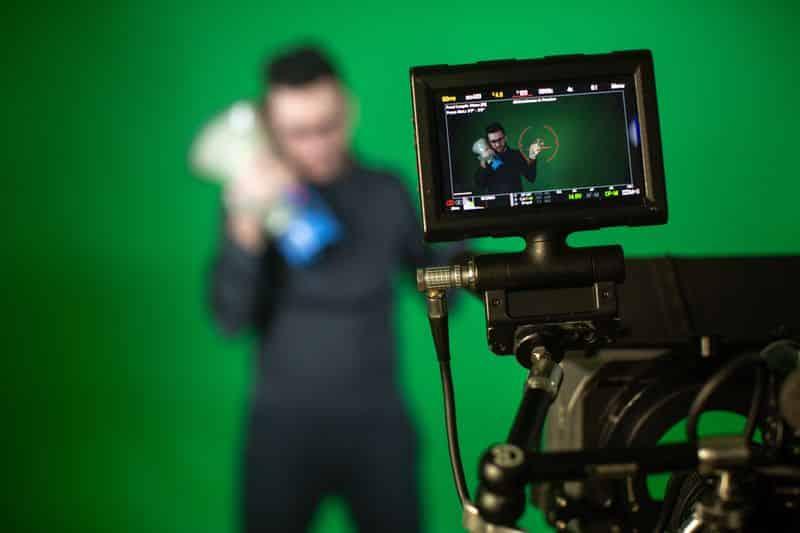 Un hombre se graba con una cámara profesional mientras sujeta un megáfono.