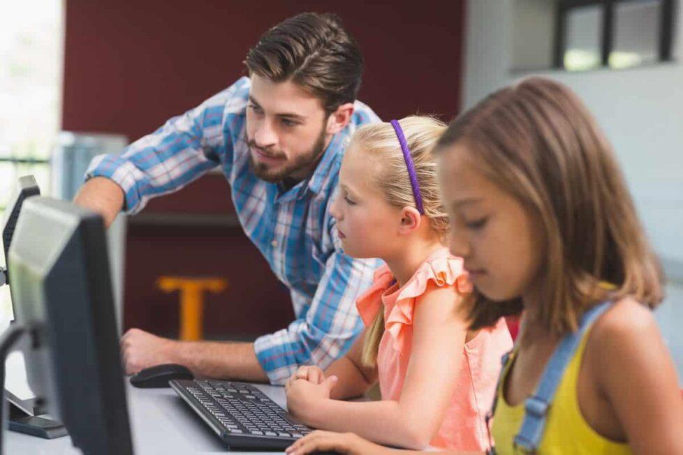 un profesor y sus alumnos usan un ordenador con soluciones de Microsoft centradas en la seguridad