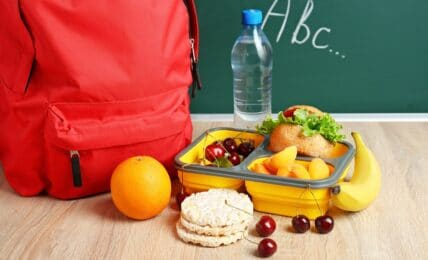 school lunch box with tasty food and backpack on table in classroom
