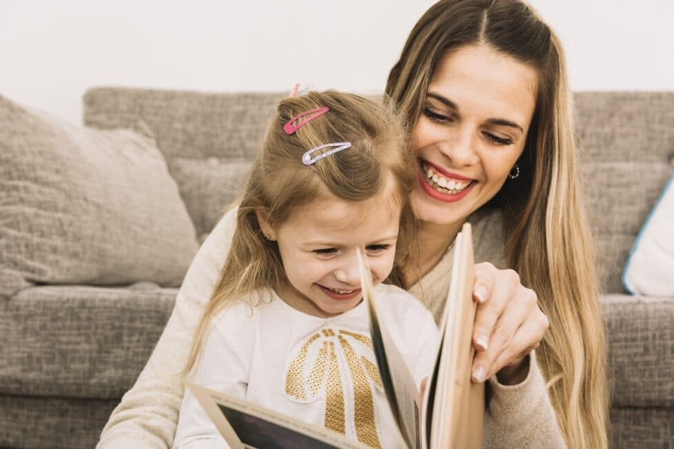cheerful mother and daughter reading book near sofa
