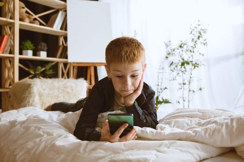 Un niño se sorprende antes el contenido de su móvil, sin vigilancia parental. - Una generación de niños y niñas pornográficos