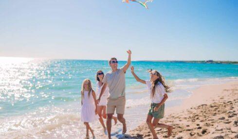 una familia juega con una cometa en la playa